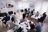 Rückansicht eines Geschäftsmannes, der während einer Videokonferenz im Büro auf den Bildschirm blickt