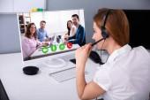 Rückansicht einer Geschäftsfrau mit Headset bei Videokonferenzen mit ihren Kollegen