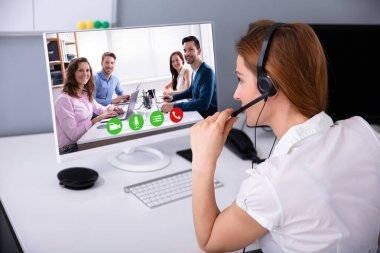 Rear View Of Businesswoman Wearing Headset While Video Conferencing With Her Colleagues
