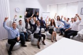 Group Of Happy Successful Multi-ethnic Businesspeople Sitting On Fitness Ball Waving Their Hands In Office