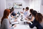 Gruppe von Geschäftsleuten bei einer Videokonferenz mit einem anderen Geschäftsteam im Amt