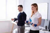 Close-up Of Male And Female Businesspeople Exercising In Office With Dumbbells