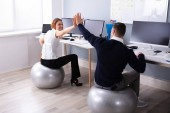 Businessman And Businesswoman Sitting On Fitness Ball Giving High Five In Office