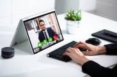 Frau mit Videochat auf Laptop im Büro