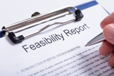 Close-up Of A Person's Finger Holding Pen Over Feasibility Report On Clipboard