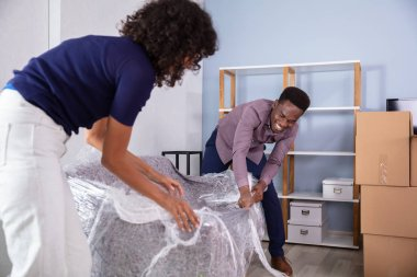 Young African Couple Unpacking Their New Sofa