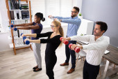 Happy Young Businesspeople Standing In Row Exercising With Dumbbells In Office