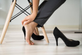 Photo Low Section Of Young Businesswoman Rubbing Her Feet In Office