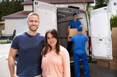 Happy Family Couple And Movers Unload Boxes From Truck