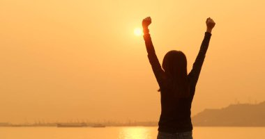 Woman raising hand up under sunset