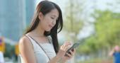 Fotografie Asijské žena pomocí aplikace na mobil v městě