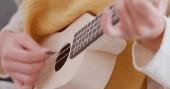 Photo Woman play on ukulele at home