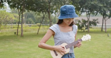 Woman play on ukulele in the park