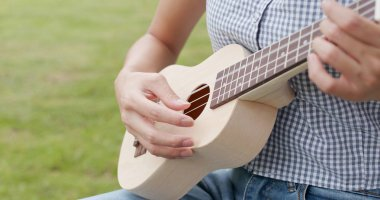 Woman play ukulele and sitting on the grass