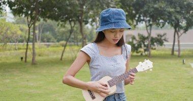 Woman playing on ukulele at city