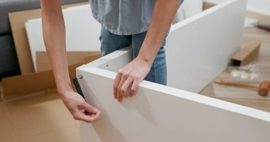 Woman assembling a shelf at home
