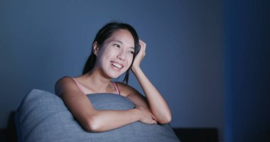 Woman watching video on computer at night