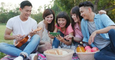 Youngster friends go picnic together at park