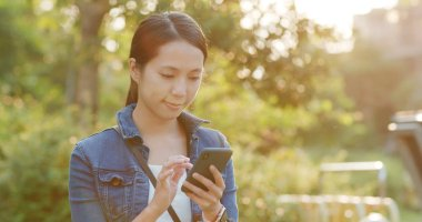 Woman look at smartphone under sunset