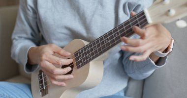 Woman play with ukulele at home