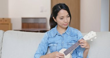 Woman enjoy play with ukulele at home