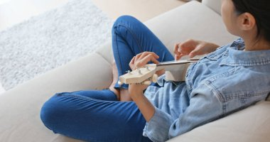 Woman sit on sofa and play with ukulele at home