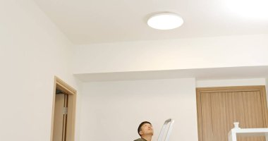 Asian Man install lamp onto the ceiling at home