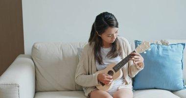 Woman play ukulele at home