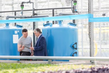 Male botanist and businessman discussing by storage tank in greenhouse