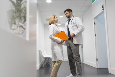 Low angle view of doctors discussing in corridor at hospital
