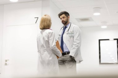 Doctors discussing while standing in corridor at hospital