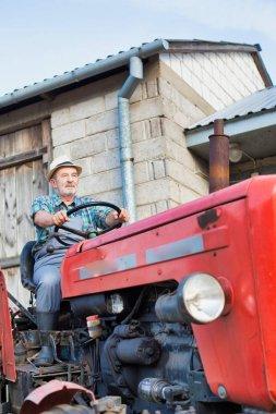 Çiftlikte traktör kullanan kendine güvenen çiftçi