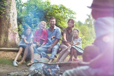 Mutlu aile parkta kamp ateşinde sosis kızartıyor.