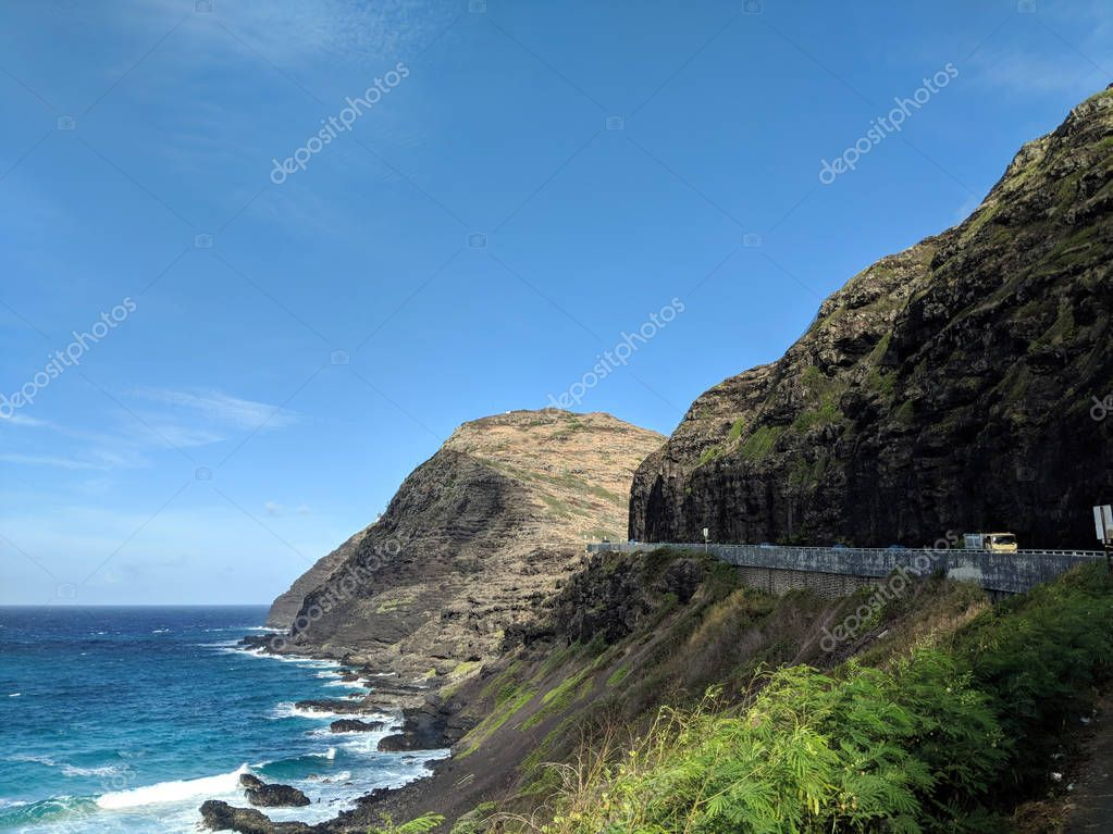 Truck Drive along cliffside mountain highway at Makapuu with stretching blue pacific ocean below on Oahu, Hawaii.