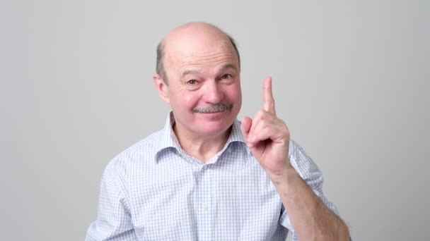 Lächelnder älterer Mann zeigt Zeigefinger in die Höhe, gibt Ratschläge