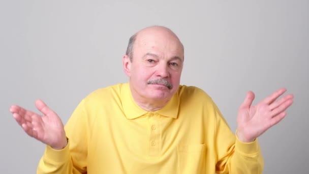 Starší muž stojící gestikuloval rukama jako že neví, co si vybrat.