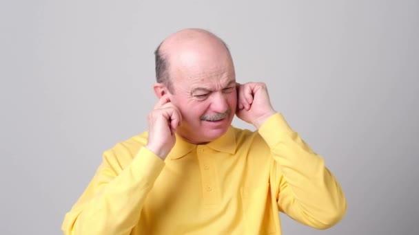 Stressbelasteter Senior verstopft Ohren mit Fingern, ignoriert laute Geräusche oder Musik