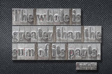 The whole is greater than the sum of its parts - ancient Greek philosopher Aristotle quote made from metallic letterpress on dark background