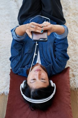 young asian woman at home choosing songs on music streaming app listening with headphones