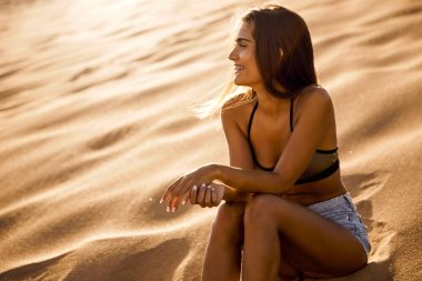 Attractive young woman sitting on sand dune
