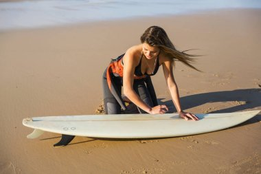 Surfer girl waxing surfboard at beach