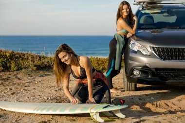 Two surfer girls near coastline with car getting ready for surfing.