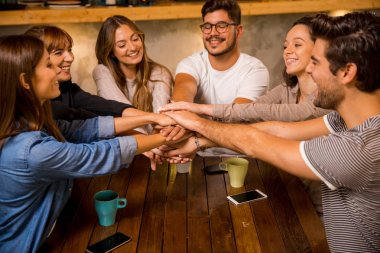 Group of friends joining their hands together at the cafe