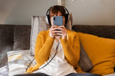 woman at home listen music on her phone