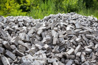 Pile of disassembled gray pavement bricks with selective focus