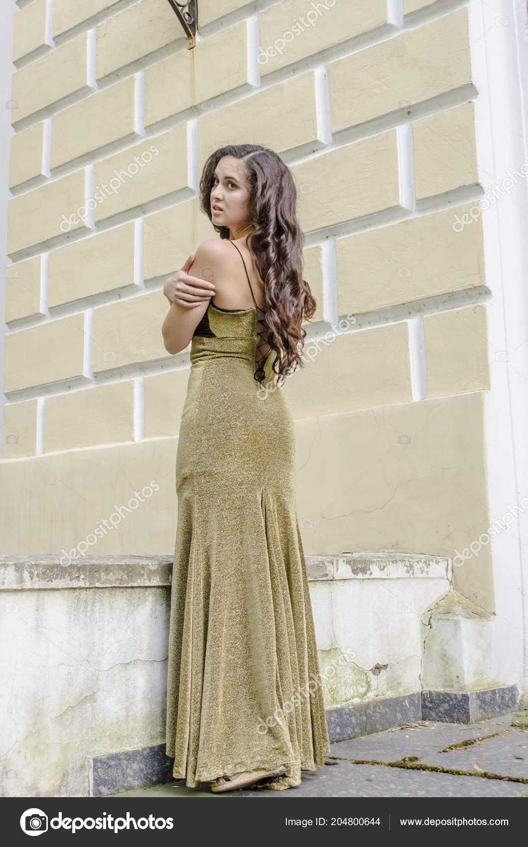 7e1be32658a3 Όμορφη μελαχρινή κοπέλα σε ένα μακρύ φόρεμα δεξίωσης από το μπαλκόνι του  παλιού σπιτιού — Εικόνα από ...