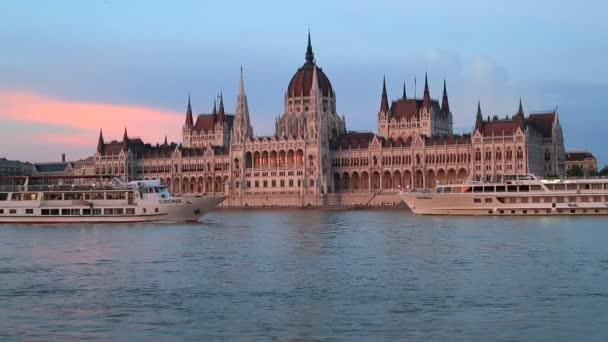 Budapest, Magyarország, június 3, 2019. Esti kilátás a Dunán folyó közlekedéséhez és a magyar Parlament épületére