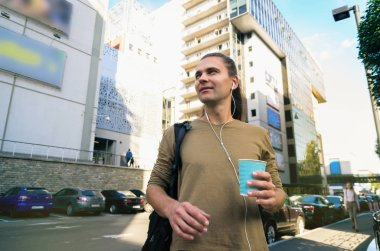 Stylish tall young man (hipster) is standing on the street of a big noisy city and drinking coffee. Life in the metropolis. Food on the go
