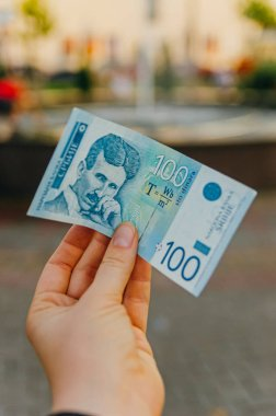 female hand holds a banknote of 100 (one hundred) Serbian dinars