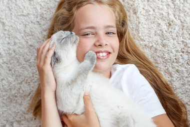 A child with a cat at home.